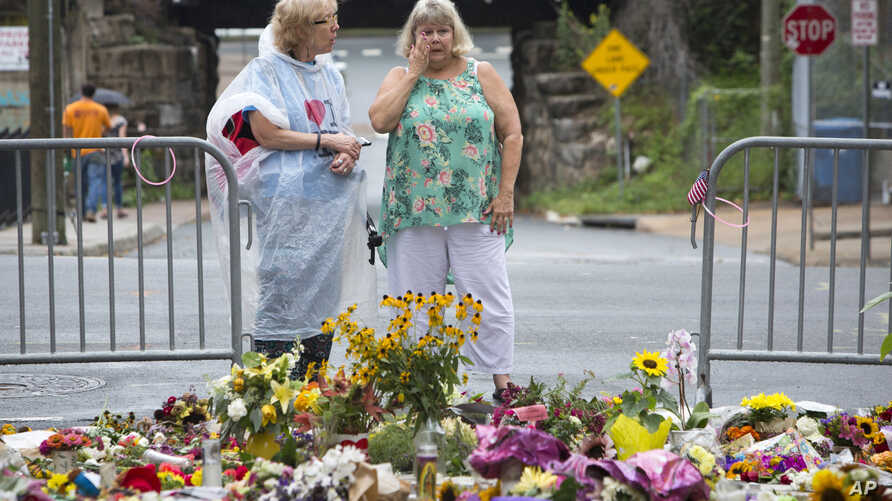 Women visit a memorial at 4th and Water Streets, Aug. 15 2017,  in Charlottesville, Va., where Heather Heyer was killed when a car rammed into a group of counterprotesters last weekend.