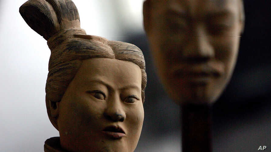 FILE - A female terracotta soldier statue holds the mask of a man as it stands in an army made up of women and children at an art gallery in Beijing, Feb. 24, 2007.  Women in China say they are seeing an eroding of their status from the days of Mao Z