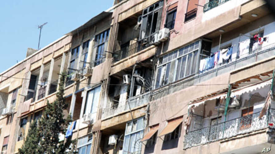 Damaged houses are seen during a heavy firefight that broke out between rebels and the Syrian government army at the western neighborhood of al-Mezze in Damascus, March 19, 2012
