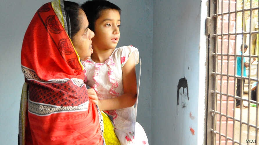 Taking her 6-year-old daughter Arwa, Sajedul Islam Shumon's wife Nasima Akhter, is standing in front of the main gate of her house in Dhaka. (A. Rajjak for VOA)