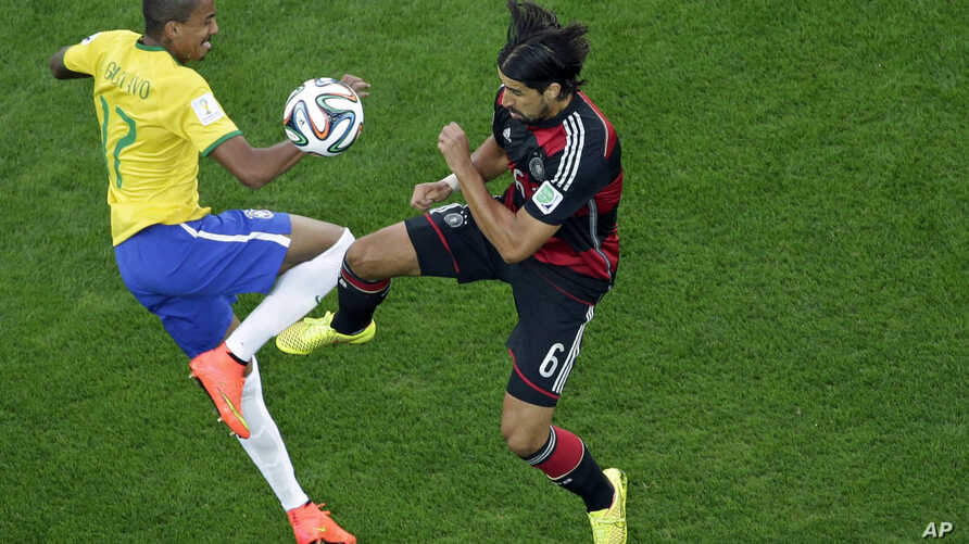 Brazil's Luiz Gustavo (l) and Germany's Sami Khedira, go for the ball during the World Cup semifinal soccer match between Brazil and Germany at the Mineirao Stadium in Belo Horizonte, Brazil, July 8, 2014.