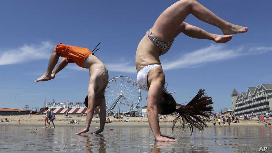 Dan Copeland, left, and Alex Morneau of Biddeford, Maine, former high school cheerleaders, perform back flips while enjoying the record breaking heat at Old Orchard Beach, Maine, May 18, 2017. The temperature climbed well into the 90s in many locatio