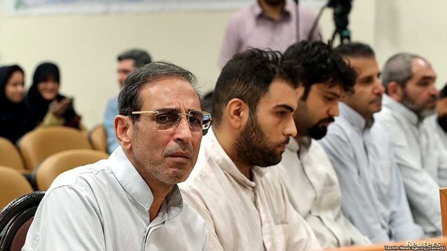 FILE - Vahid Mazloumin (L) is seen appearing in court for the first time on charges of manipulating the currency market. He was later sentenced to death, in Tehran, Sept. 8, 2018