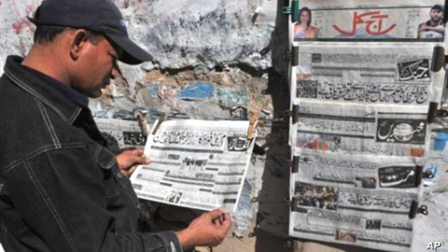 A Pakistani man reads an Urdu-language evening newspaper reporting the capture of a top Taliban commander at a news stand in Karachi, 16 Feb 2010