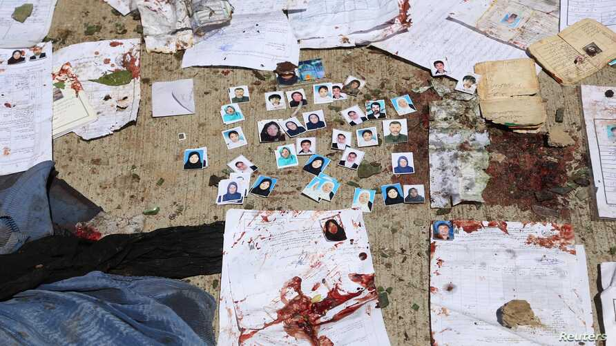 Blood-stained national ID papers and voters' photos are seen on the ground outside a voter registration center after a suicide attack in Kabul, April 22, 2018.