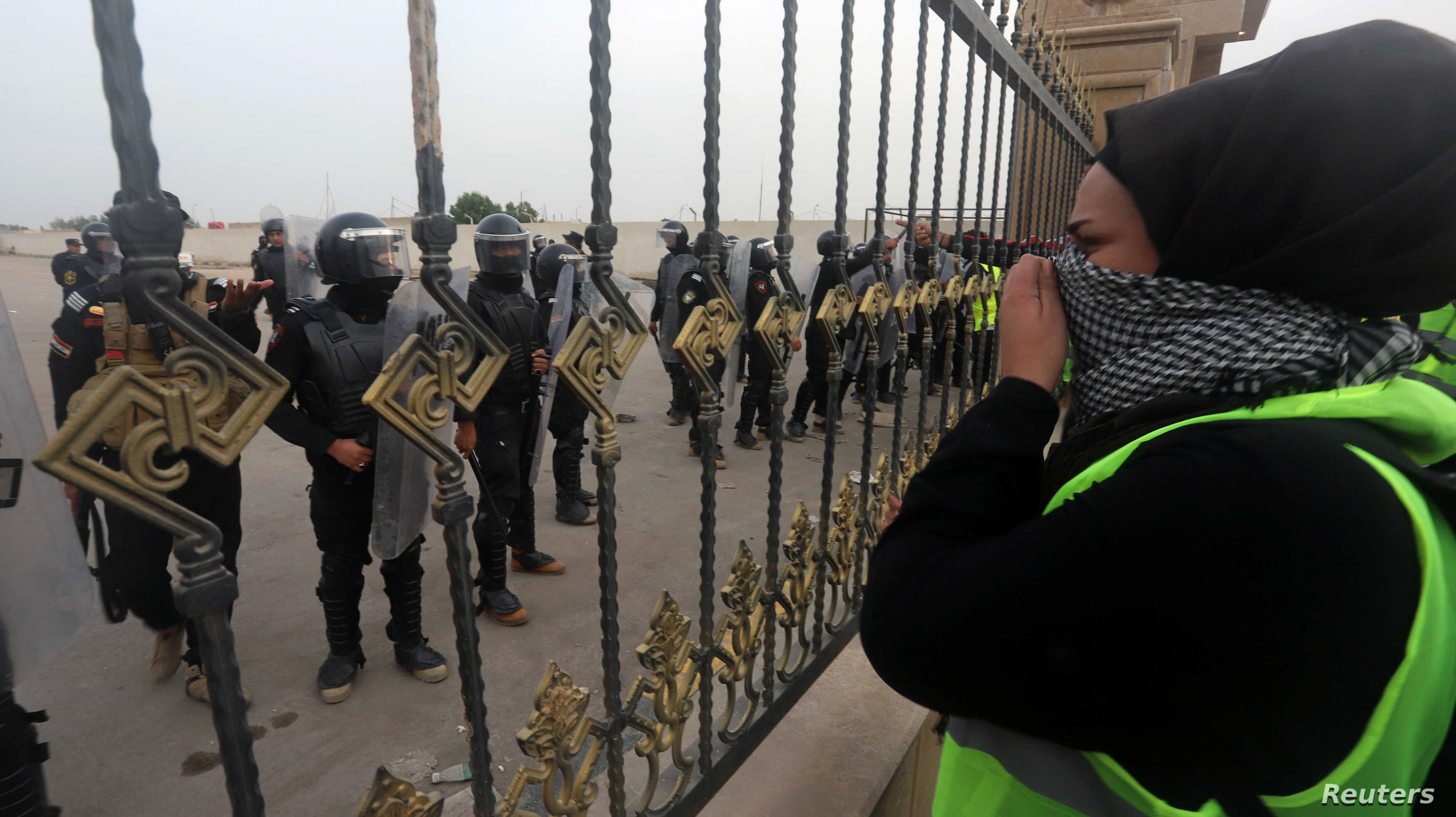 Iraqi demonstrators stand in front of Iraqi security forces during an anti-government protest near the government building in Basra, Iraq Dec. 4, 2018.
