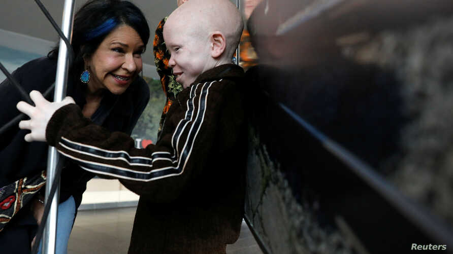 Elissa Montanti, founder of the Global Medical Relief Fund, talks with Baraka Lusambo, a Tanzanian with Albinism visiting the U.S. for medical care, after his arrival at JFK International Airport in New York City, March 25, 2017.