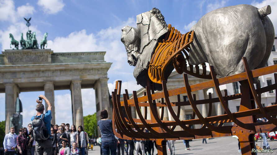 """A man takes a picture near a piece of a traveling art exhibition called """"Lapidarium, Waiting for the Barbarians"""" by Mexican artist Gustavo Aceves, in front of Brandenburg Gate in Berlin, Germany, May 4, 2015."""