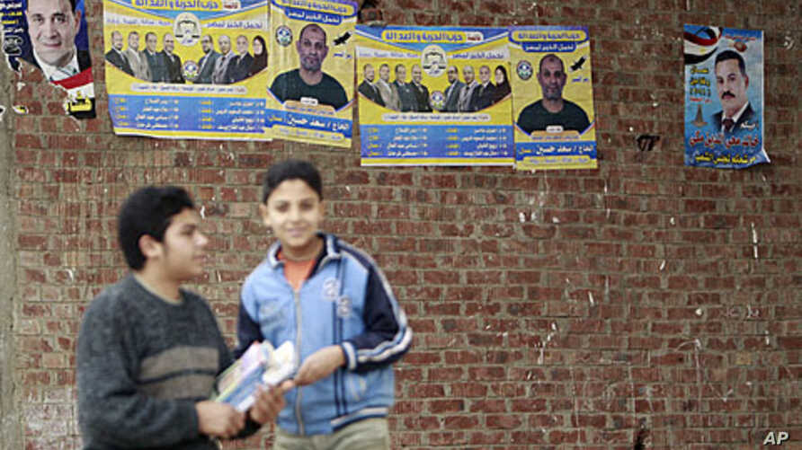 Boys stand near campaign posters of the Muslim Brotherhood's Freedom and Justice Party outside a polling station during the second day of parliamentary elections in the village of Kafr el-Moseilha, the hometown of former president Hosni Mubarak, Dece