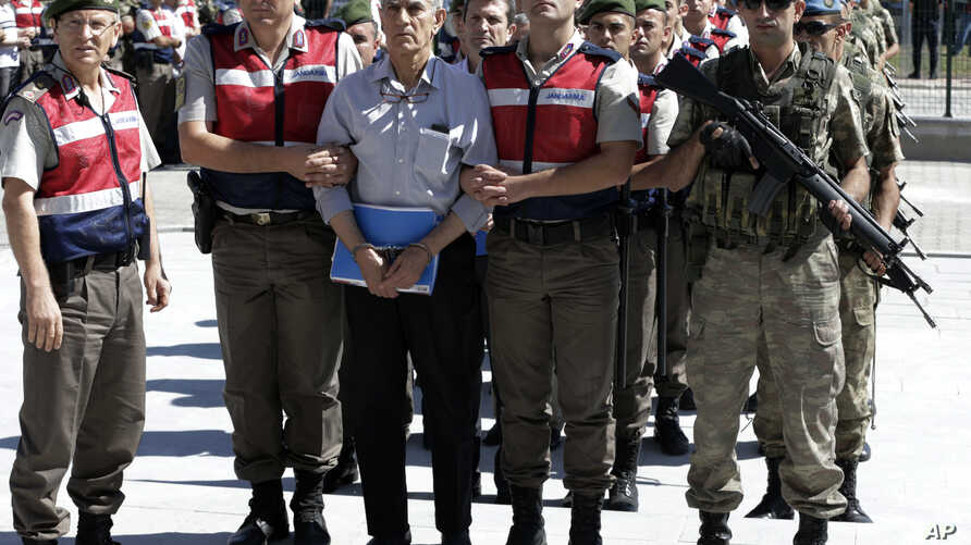 FILE - paramilitary police and members of the special forces escort former Air Force commander Akin Ozturk and other suspects of last year's failed coup, outside the courthouse at the start of a trial, in Ankara, Turkey.