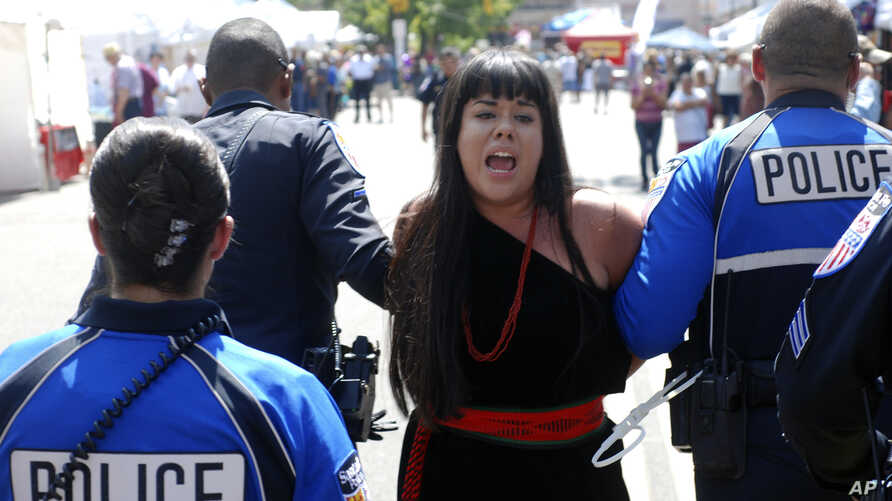 Police in Santa Fe, N.M., lead away protester organizer Jennifer Marley of San Ildefonso Pueblo in hand restraints, Sept. 8, 2017. Santa Fe police say they arrested at least 12 people to contain protest against an annual pageant marking the return of