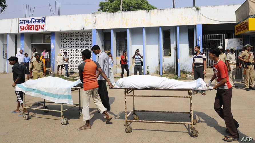 Volunteers and hospital staff transport the bodies of killed Indian Central Reserve Police Force personnel at a hospital in Gaya, October 18, 2012.