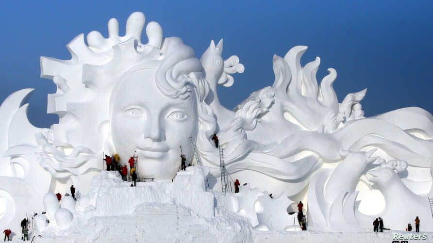 FILE - Artists work on snow sculptures at an exhibition in Harbin, Heilongjiang province, China, Dec. 13, 2016.