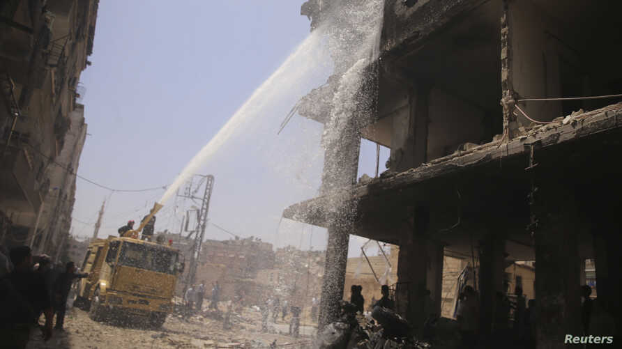 Civil defence members try to put out a fire after what activists claim was a car explosion in a market in central Douma in the eastern al-Ghouta, near Damascus June 28, 2014