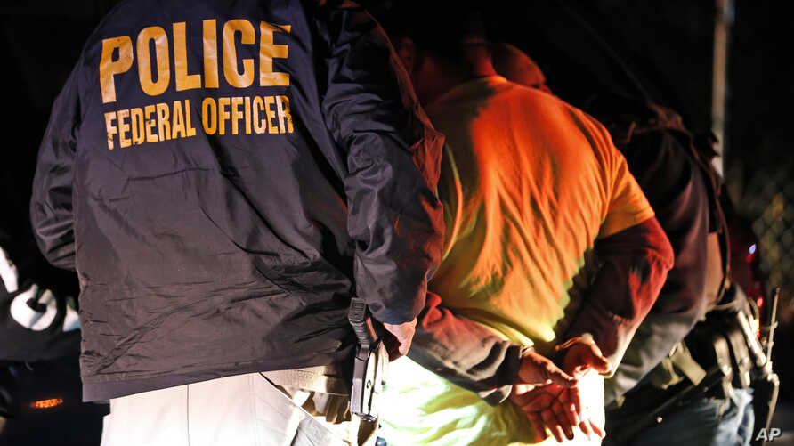 FILE - In this Oct. 22, 2018, photo U.S. Immigration and Customs Enforcement agents surround and detain a person during a raid in Richmond, Va.