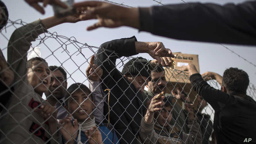 Displaced Iraqis gather by the fence to buy food and supplies from vendors standing outside the Chamakor camp, east of Mosul, Iraq, March 12, 2017.