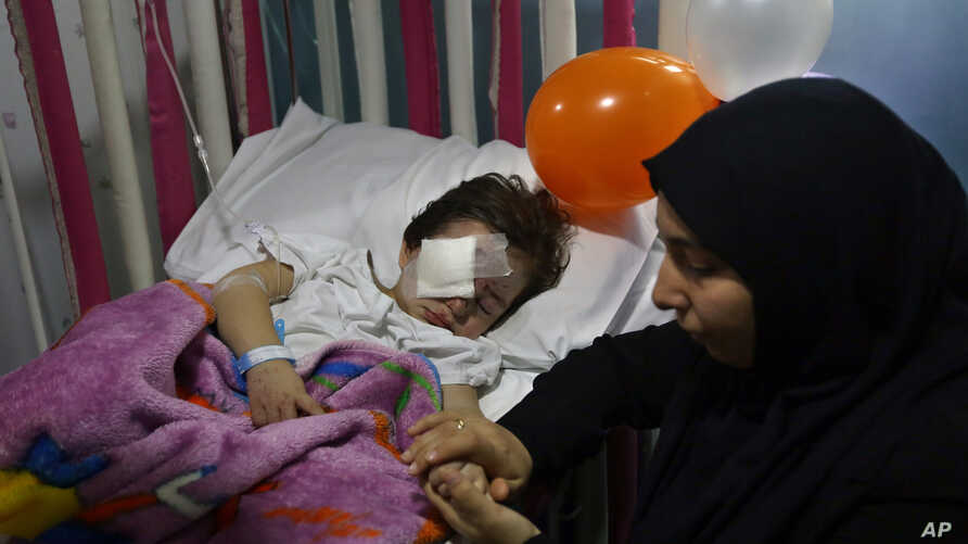 Adraa Taleb holds the hand of her maternal cousin Haidar Mustafa, three, who was wounded in Thursday's twin suicide bombings, as he sleeps on a bed at the Rasoul Aazam Hospital in Burj al-Barajneh, southern Beirut, Lebanon, Friday, Nov. 13, 2015.