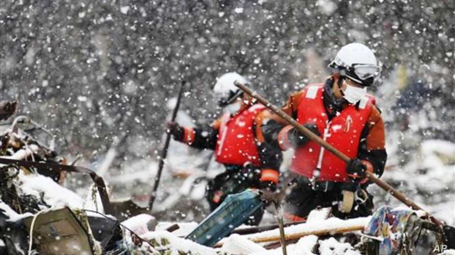 Snow falls as rescue workers in Japan search for victims of earthquake and tsunami