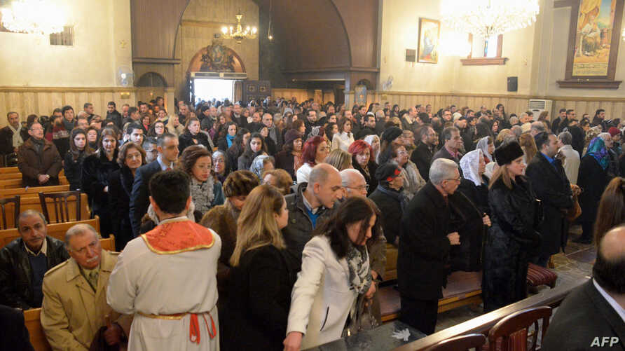FILE - Armenian Orthodox worshippers attend a Christmas service at the Holy Mother of God Armenian Orthodox Church on Jan. 6, 2016 in the northern Syrian city of Aleppo.