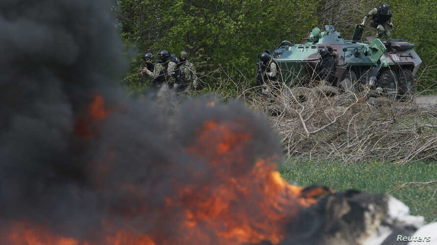 Ukrainian security force officers are deployed at a checkpoint set on fire and left by pro-Russian separatists near Slovyansk, April 24, 2014.