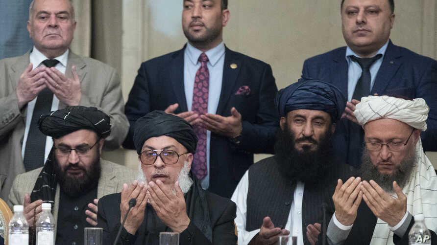 Taliban political chief Sher Muhammad AbbasStanikzai, in the first row, second from left, Abdul Salam Hanafi and other Taliban officials pray during the intra-Afghan talks in Moscow, Feb. 6, 2019.