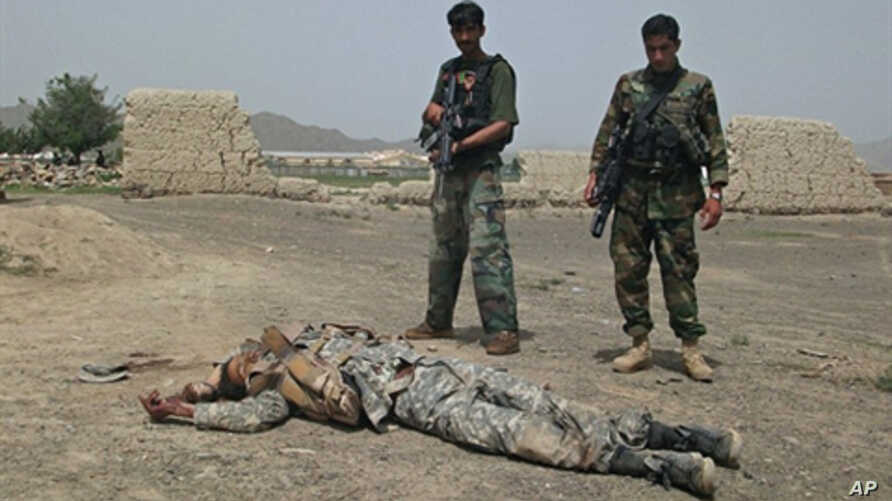 Afghan National Army (ANA) soldiers stand guard near the body of a suicide attacker near US military camp Salerno on the outskirts of Khost city, 28 Aug 2010