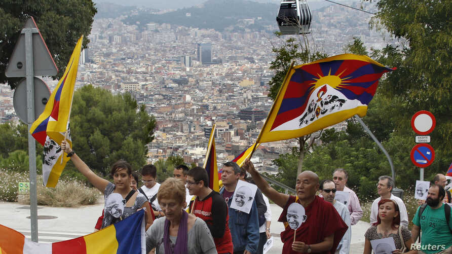 """Buddhist monk Thubten Wangchen (3rd R) and participants walk with Tibetan flags and images of Mahatma Gandhi during their march for """"peace and non-violence"""" from Plaza d'Espanya [Spain Circus] to the Montjuich castle in Barcelona October 2, 2010."""
