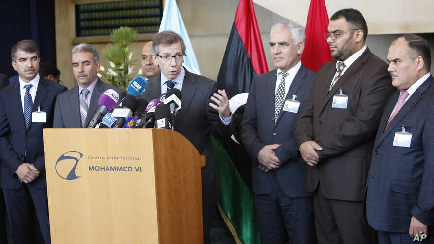 U.N. representative for Libya, Bernardino Leon, center, addresses reporters while Libyan parliaments members listen in Rabat, Morocco,  Sept. 18, 2015..