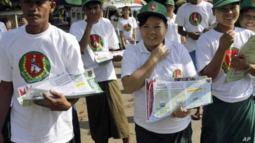 Members of the Union Solidarity and Development Party walk to distribute the party's leaflets for the upcoming general elections in Yangon, Burma. The general elections take place Nov. 7, the first in 20 years.