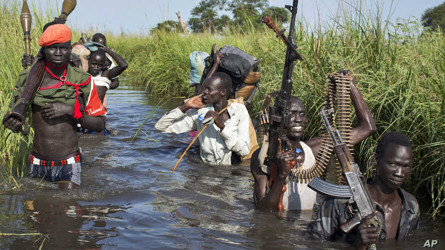 Rebel soldiers patrol and protect civilians from the Nuer ethnic group as the civilians walk through flooded areas to reach a makeshift camp for the displaced situated in the United Nations Mission in South Sudan (UNMISS) base in the town of Bentiu,