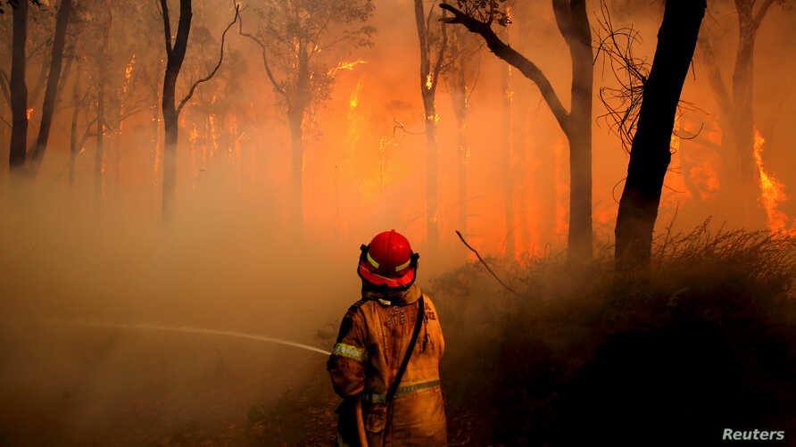 A New South Wales (NSW) Rural Fire Service firefighter sprays water on a bushfire in the suburb known as Salt Ash, located north of Newcastle in Australia, Nov. 23, 2018.