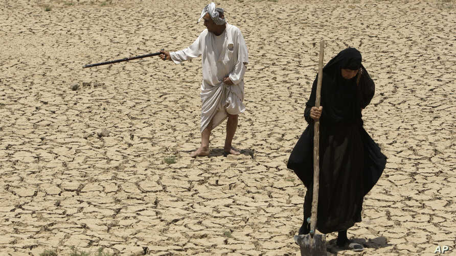 Adilla Finchaan, 50, and her husband, Ashore Mohammed, 60 walk their dried-up farmland in Iraq in this 2009 photograph. The Tigris-Euphrates region suffered consecutive years of drought.