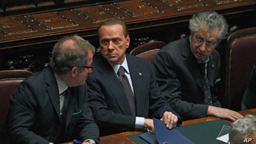 "Italian Prime Minister Silvio Berlusconi (C) holds and saves a memo reading ""308 [the result of the vote] - 8 traitors - political reversal - vote - take note: resign - Republic President - a solution"" during a budget vote at the parliament in Rome,"