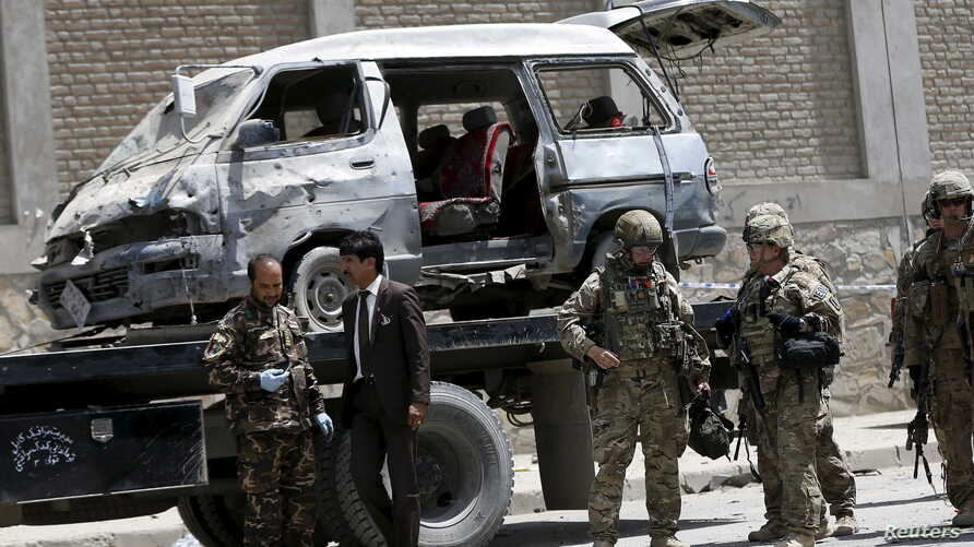 Afghan and foreign security forces keep watch at the site of car bomb attack in Kabul, May 17, 2015.