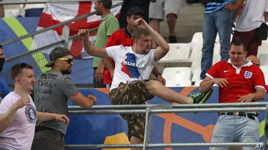 FILE - In this Saturday, June 11, 2016 file photo, Russian supporters attack an England fan at the end of the Euro 2016 Group B soccer match between England and Russia, at the Velodrome stadium in Marseille, France.