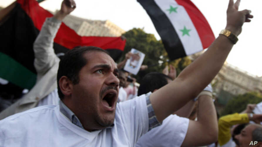 Protesters chant slogans during an anti-Syrian regime protest in front of the Arab League headquarters in Cairo, Sunday, Oct. 16, 2011.