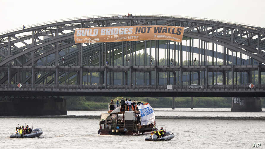 "Activists of the refugee support group SeaWatch attach a poster that reads ""Build bridges not walls"" to a bridge over the river Elbe in Hamburg, Germany, June 28, 2017. Hamburg will host a G-20 summit July 7-8."