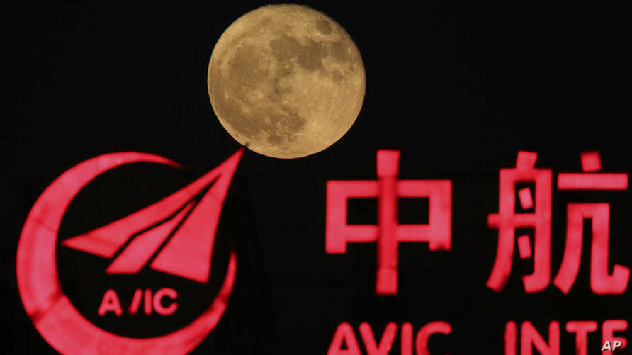 The supermoon, rises over a logo for AVIC or Aviation Industry Corp in Beijing, China, Tuesday, Nov. 15, 2016. AVIC is a Chinese state-owned corporate colossus with 500,000 employees and 140 subsidiaries in businesses ranging from aircraft manufactur