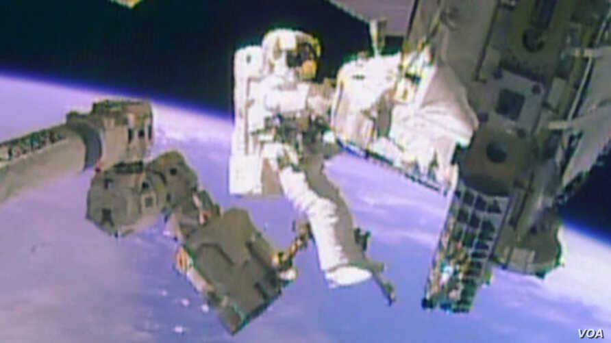 Astronaut Mike Hopkins works outside the International Space Station during a spacewalk, December 24, 2013, in this still image taken from video courtesy of NASA. Two NASA astronauts floated outside the International Space Station on Tuesday for a se