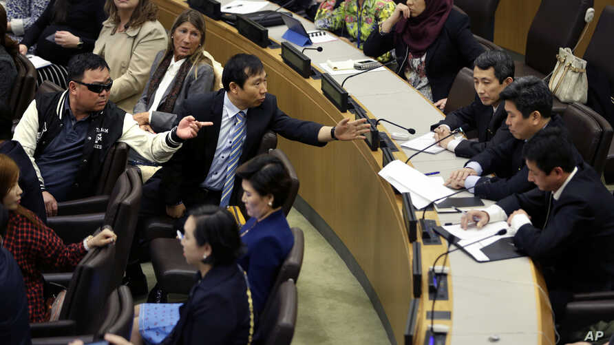 North Korean defectors, left, argue with North Korean diplomats, right, at United Nations headquarters as the diplomats try to make a statement during a panel discussion on North Korean human rights abuses, April 30, 2015.