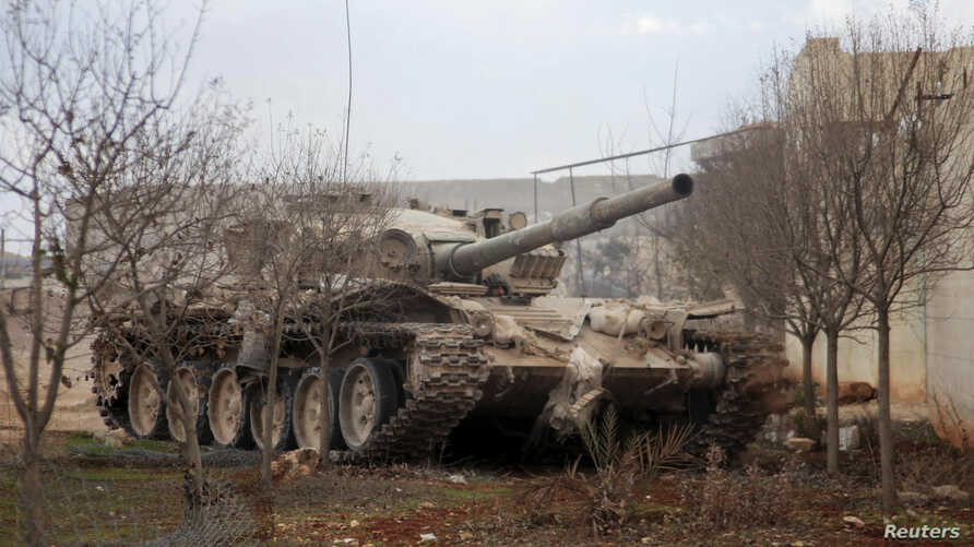 A Syrian Army soldier loyal to Syria's President Bashar al-Assad is pictured in a tank in Ard al-Hamra in Aleppo, after claiming to have regained control of the area February 27, 2014. REUTERS/George Ourfalian (SYRIA - Tags: POLITICS CIVIL UNREST CON