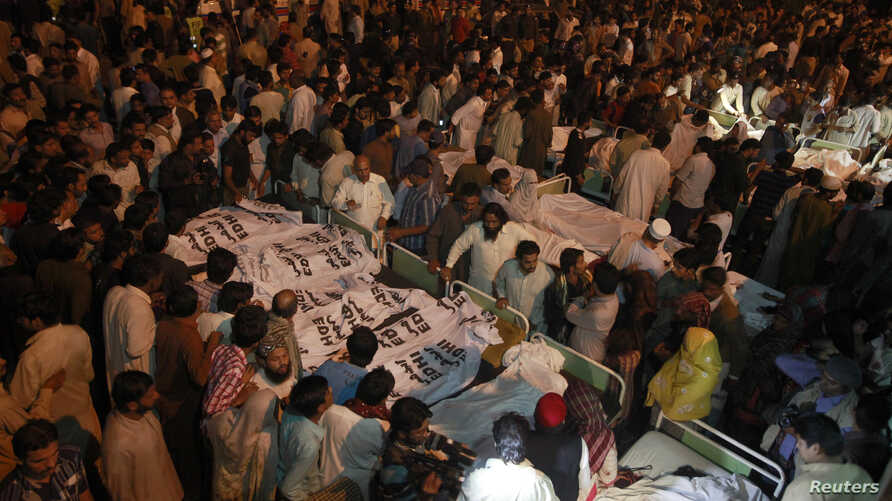 Pakistani relatives gather beside the covered bodies of victims who were killed in suicide bomb attack in Wagah border near Lahore, Nov. 2, 2014.