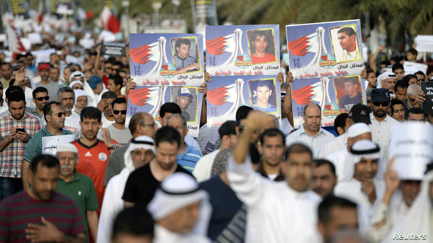 Protesters hold banners as they shout anti-government slogans during a protest in Budaiya west of Manama, Bahrain, April 4, 2014.
