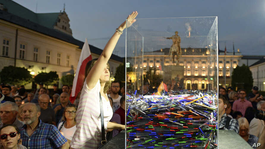 Protesters throw away pens in front of the Presidential Palace to show President Andrzej Duda their disapproval after he signed the latest legislation on the Supreme Court into law, in Warsaw, Poland,  July 26, 2018.