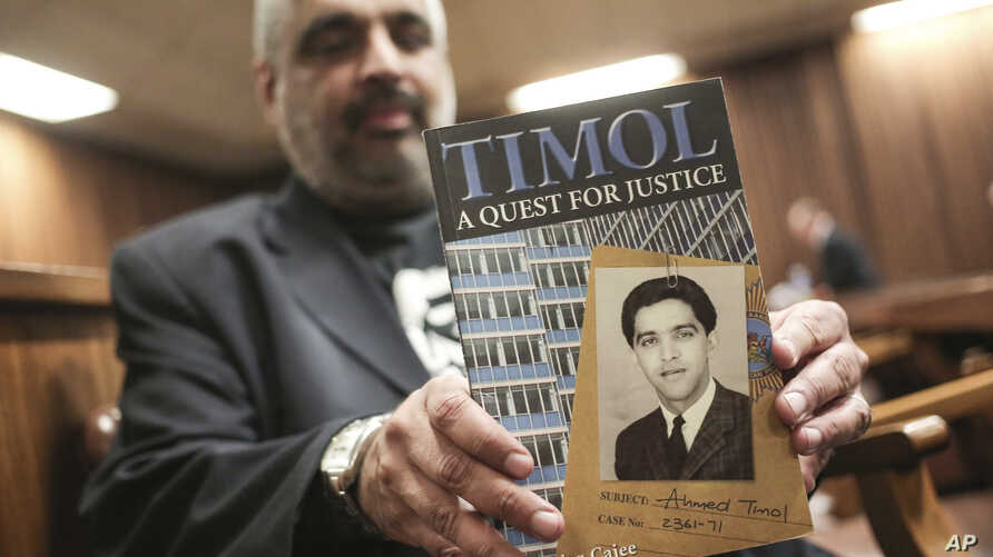"""Imtiaz Cajee, nephew of Ahmed Timol, poses with his book """"Timol, A Quest for Justice"""" in the North Gauteng High court in Pretoria, South Africa, Thursday, Aug. 24, 2017 after the court heard the final arguments in the inquest into the death of anti-a"""