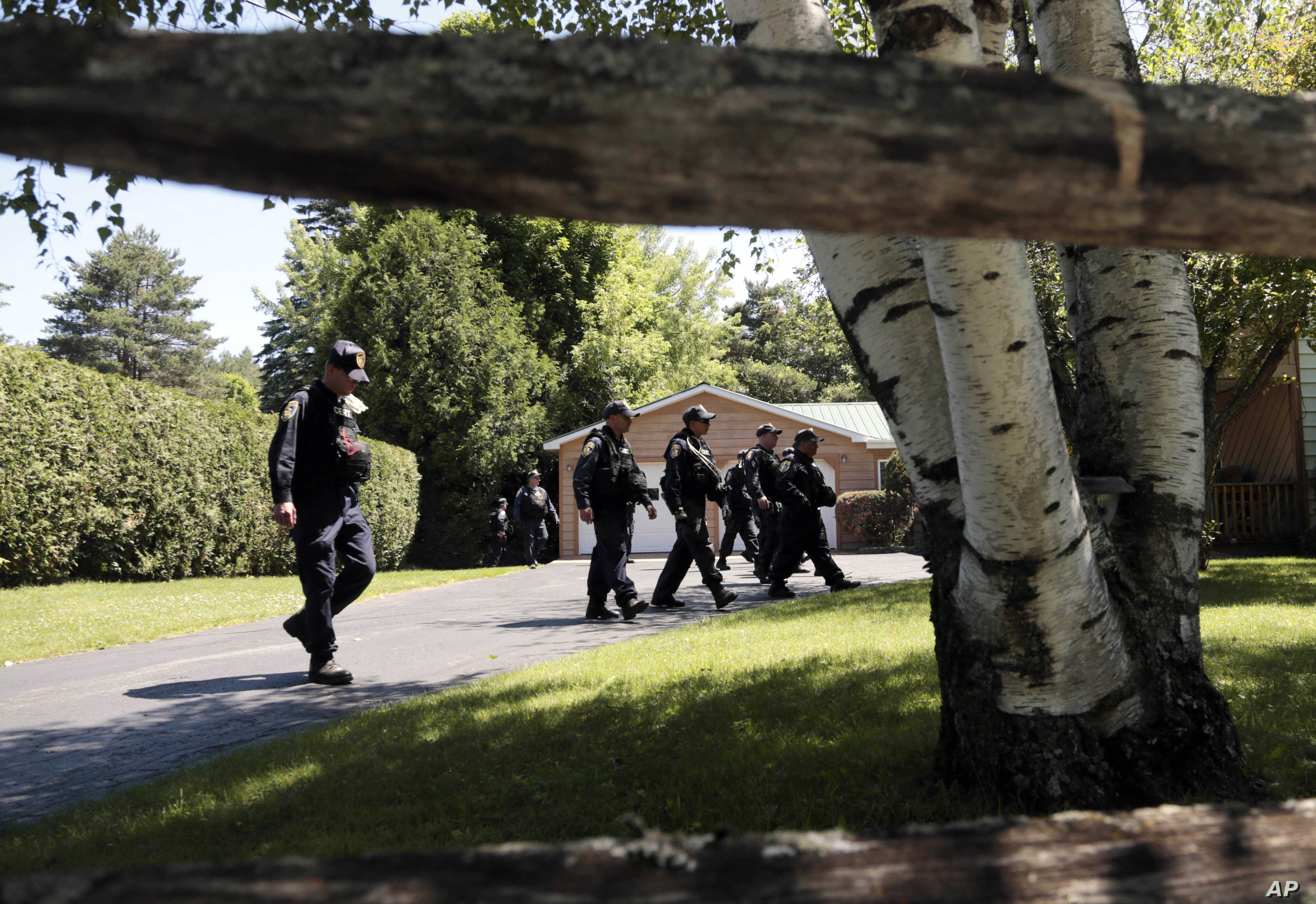 Corrections officers walk through a residential area in Malone, N.Y., during a search for two escaped prisoners from the Clinton Correctional Facility, June 24, 2015,