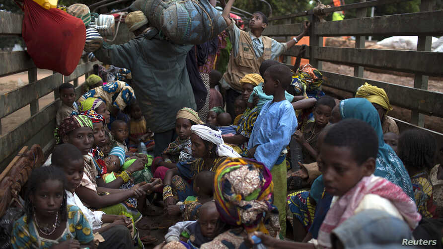 FILE - People, consisting mostly of women and children, sit at the back of a truck as the prepare to flee sectarian violence in a convoy escorted by African Union (AU) peacekeepers towards the border with Cameroon, in the town of Bouar, west of the C