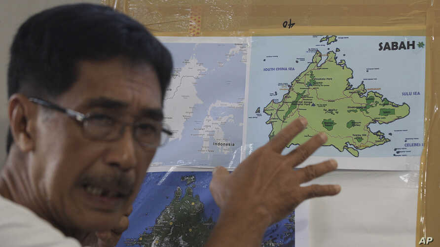 Abraham Idjirani, spokesman for the Sultanate of Sulu, points at a map of Borneo's eastern Sabah state as he talks to reporters in suburban Taguig, south of Manila, Philippines, March 5, 2013.