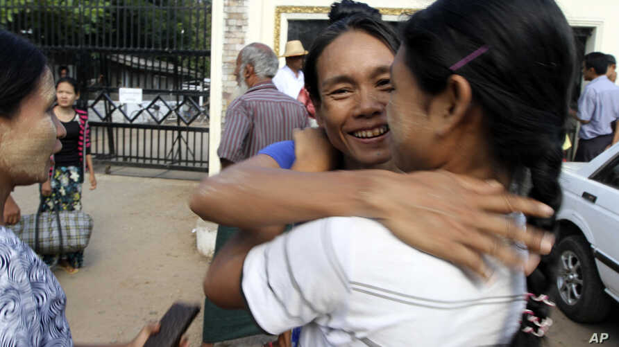 A prisoner, center, is welcomed by her relative outside Insein prison in Rangoon after the government released prisoners Nov. 15, 2012.