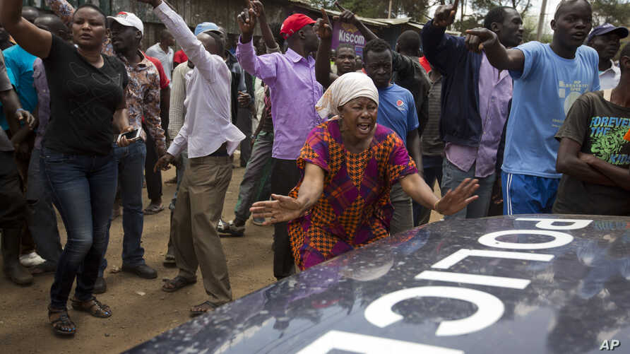 The crowd directs a police vehicle to leave as they demand the resignation of a local police officer because of police cruelty on the previous day, in Kibera slum in Nairobi, Kenya, Oct. 27, 2017.